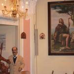La statua lignea di San Rocco con il suo realizzatore e sullo sfondo il Dipinto di Edgardo Rossaro raffigurante il Santo.